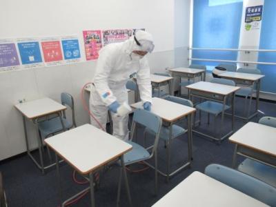 本格的な作業服で1つ1つの机、いすなどを丁寧に除菌
